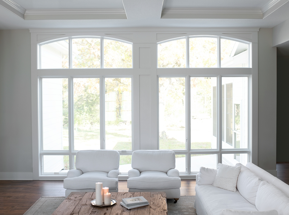 White living room with tall floor to ceiling special shape windows