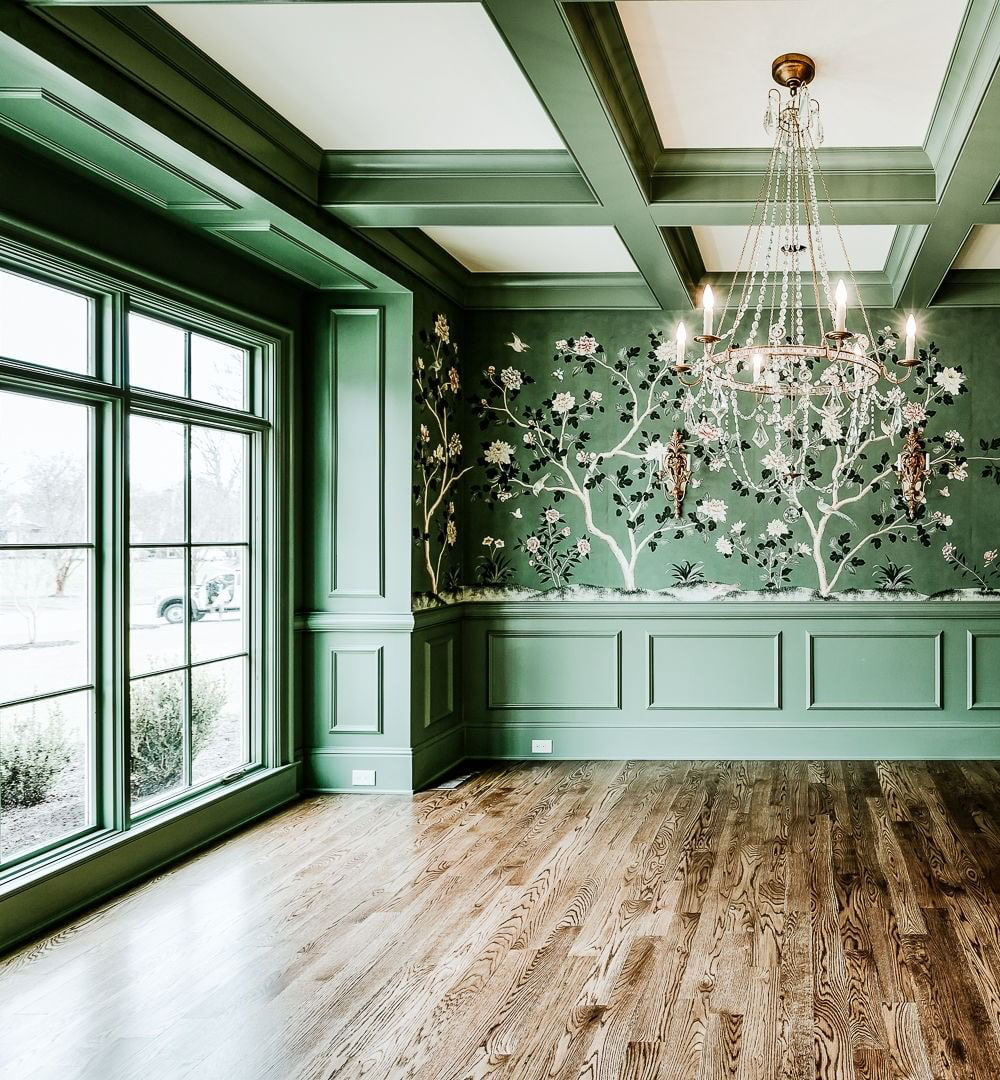 An emerald green dining room features custom wood windows painted green to match the walls.