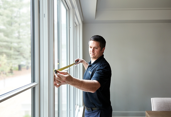 man measuring a window with tape measure