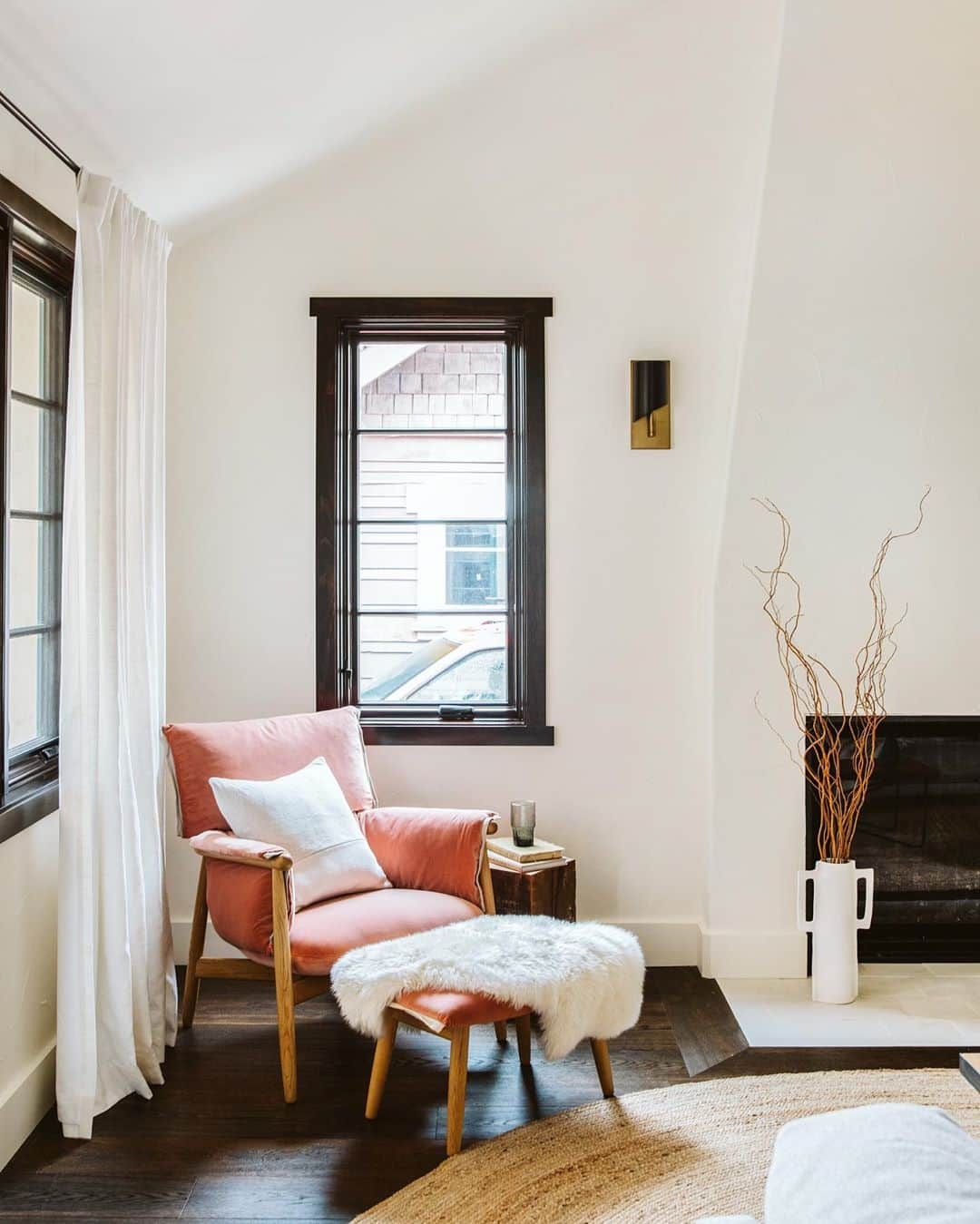 corner of living room with black casement window and red upholstered chair