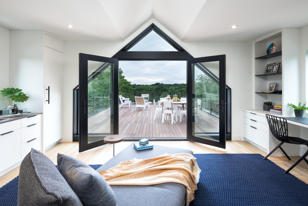black french doors paired with special shape windows create triangle entryway to backyard patio