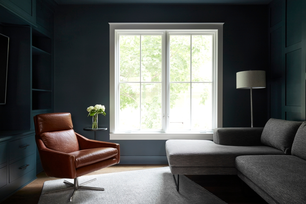 dark living room walls contrasts with two white casement windows and brown leather chair