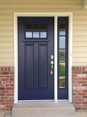 Navy blue craftsman style front door with attached sidelight on the right hand side