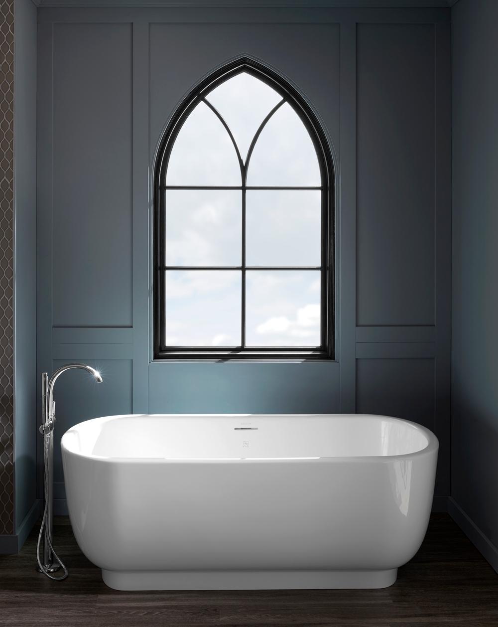 dark gray bathroom walls, white freestanding tub, and black custom shape window overhead