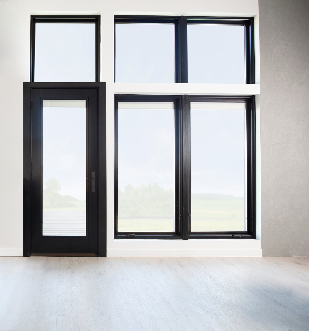 black windows surround black hinged patio door taking entire wall in modern living room