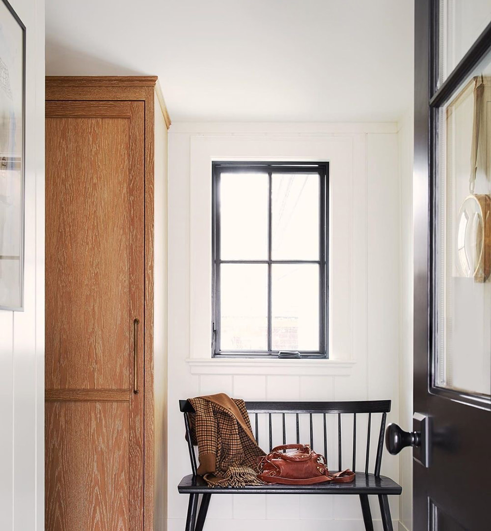 A black casement window above a bench in an entryway.