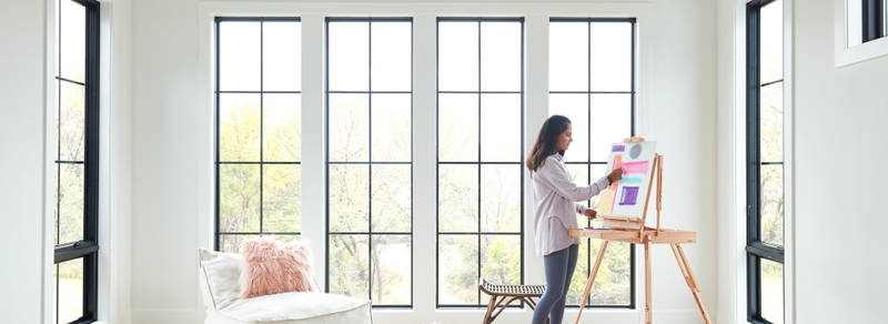 young woman painting surrounded by several pella black-trimmed windows