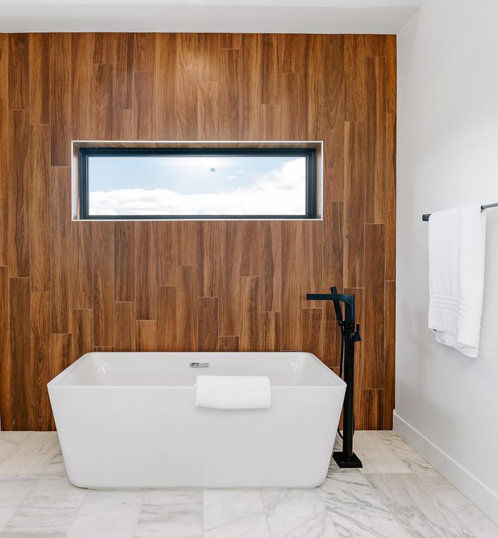 A wood accent wall features a rectangular picture window above a bathtub.