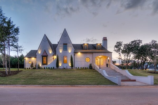 New construction home with custom shape windows lit up at dusk
