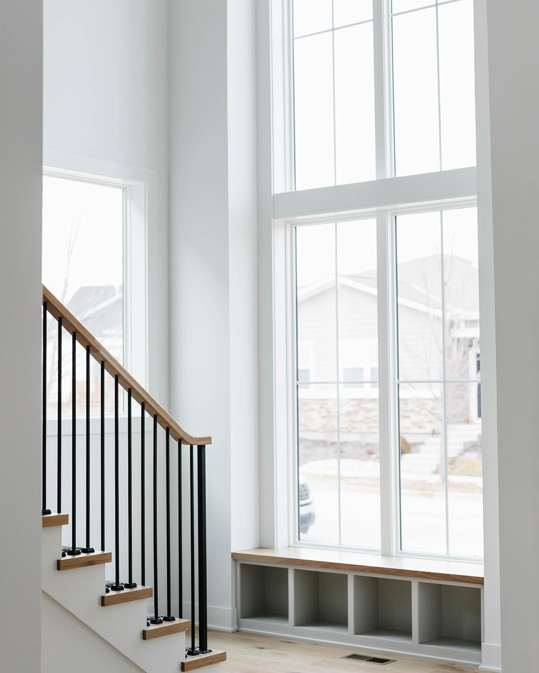 stacked picture windows with shoe cubbies underneath at the bottom of stairs