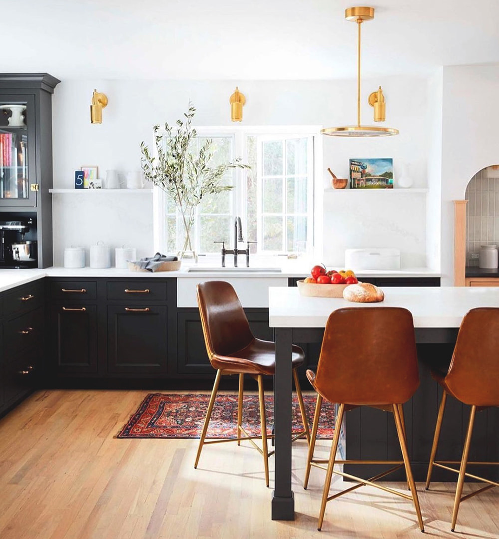 Traditional kitchen features dark cabinets with gold hardware and white casement windows behind the sink.