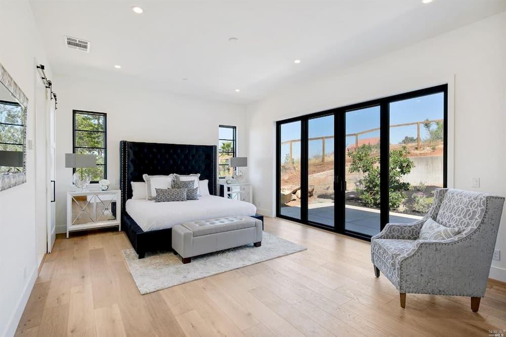 Black sliding french doors set in bright white bedroom