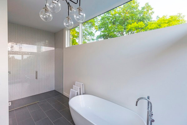 White modern bathroom with glass shower frame, white tub, and high fixed windows