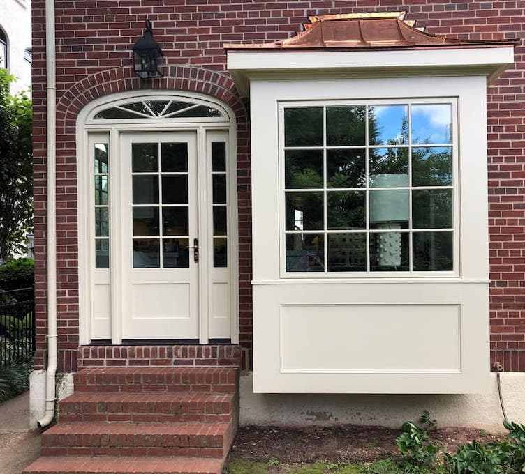 Tan picture window and custom hinged patio door with sidelights and transom on brick home