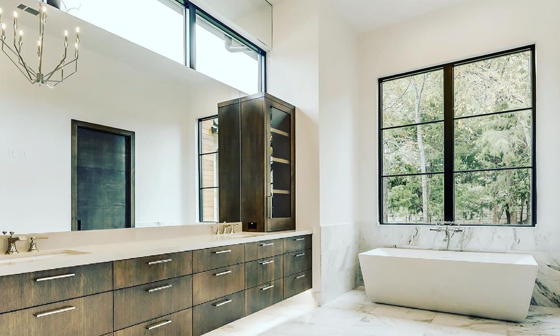 A contemporary bathroom with black picture windows over the white bathtub and wood vanity.