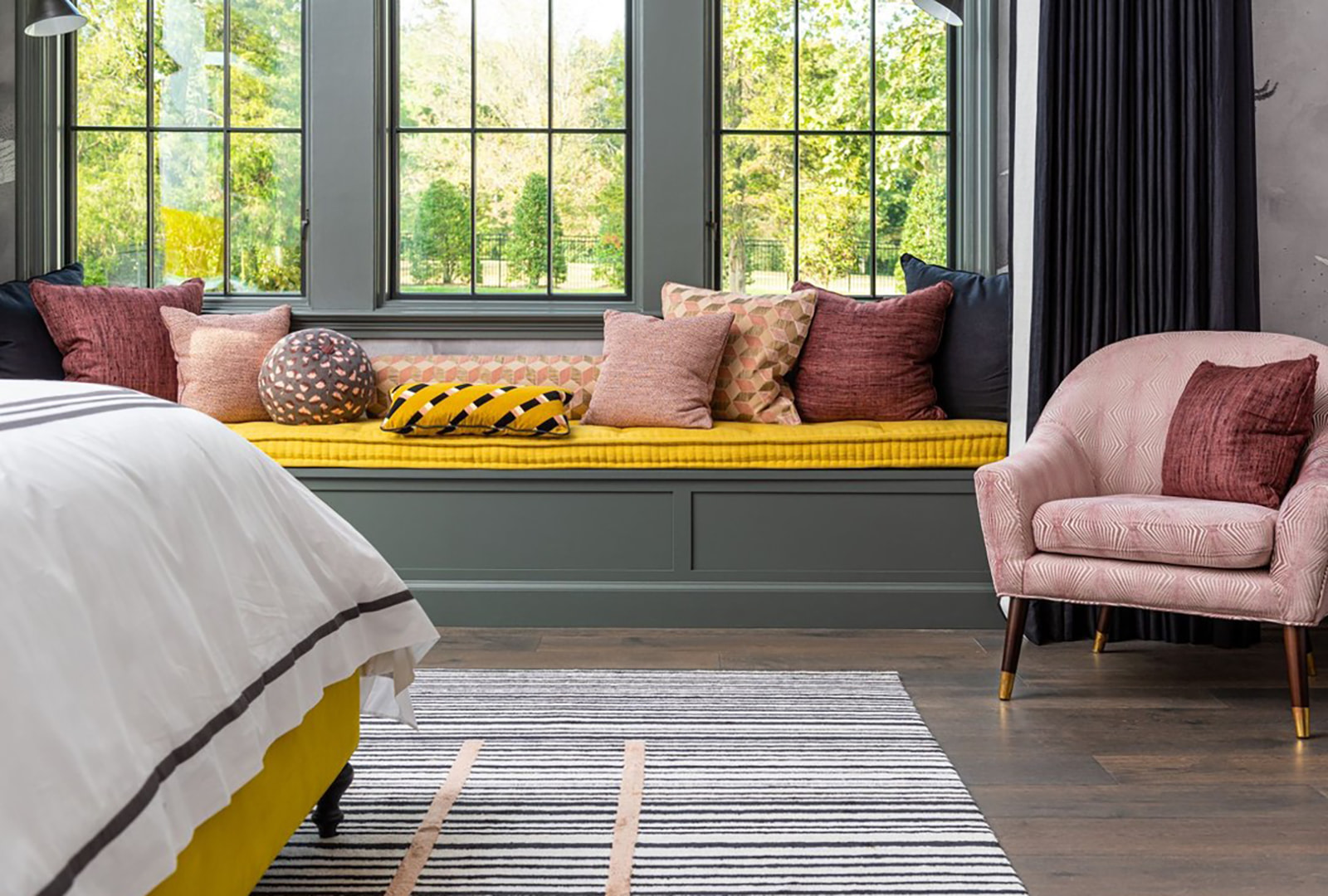 A modern bedroom with pink and yellow décor, and three windows above a seating area.