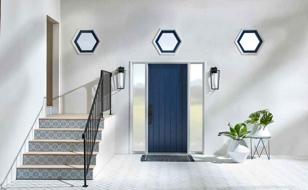 gray entryway with navy front door, mosaic tile steps, and three hexagon shape windows above the doorway