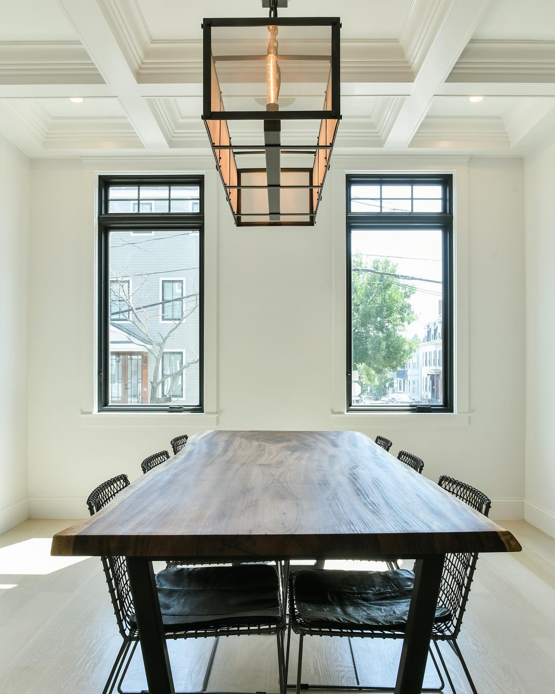 Contemporary dining room brightened by two casement windows with small fixed windows overhead
