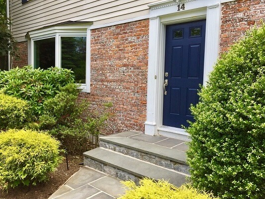 Navy blue front door with white trim has large green bushes on either side