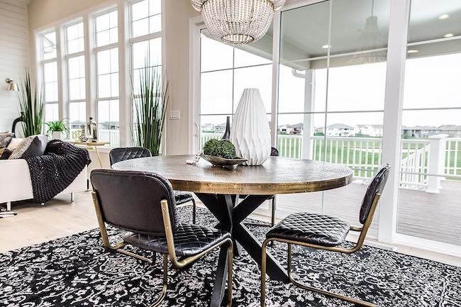 A traditional dining room and living room space has white wood windows and a patio door that occupy a full wall.