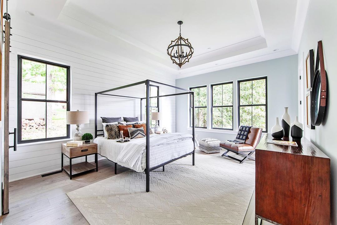 contemporary bedroom with four poster bed, chandelier, and black double-hung windows