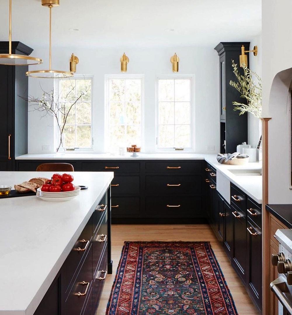 Three white casement windows sit between dark cabinets in traditional kitchen.