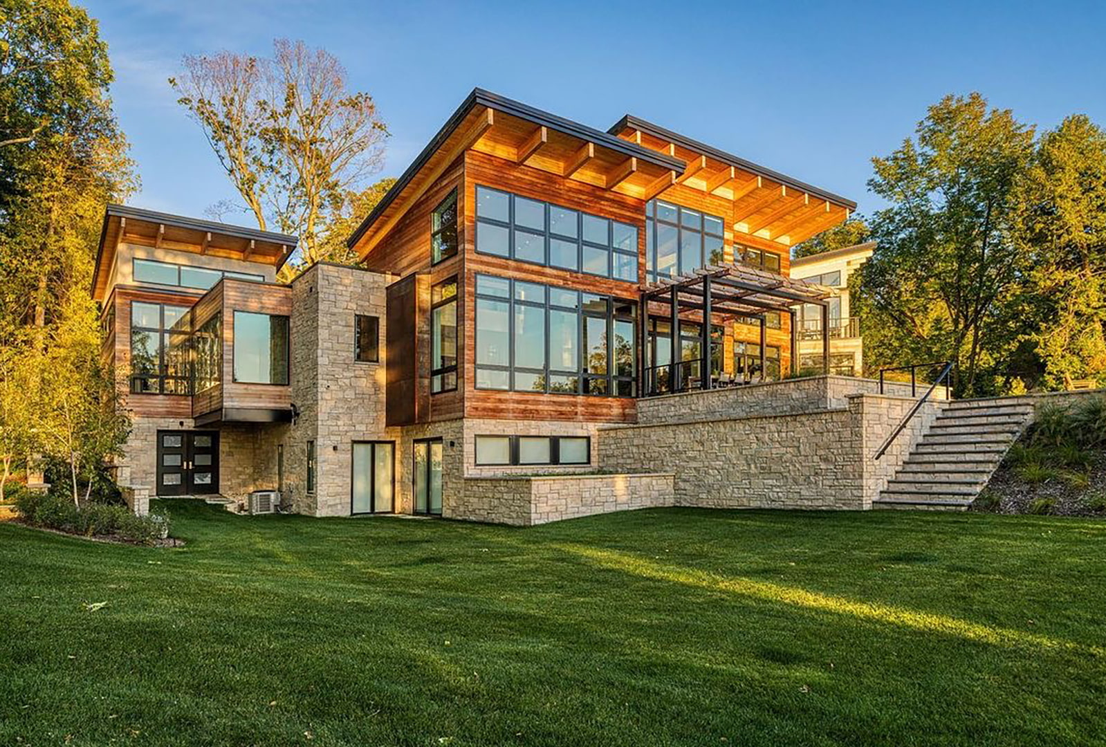 A modern home has wood siding, stonework and walls of black windows and sliding patio doors.