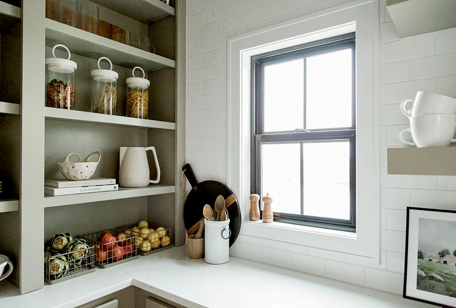 A black single-hung window in the corner of a farmhouse-style kitchen.