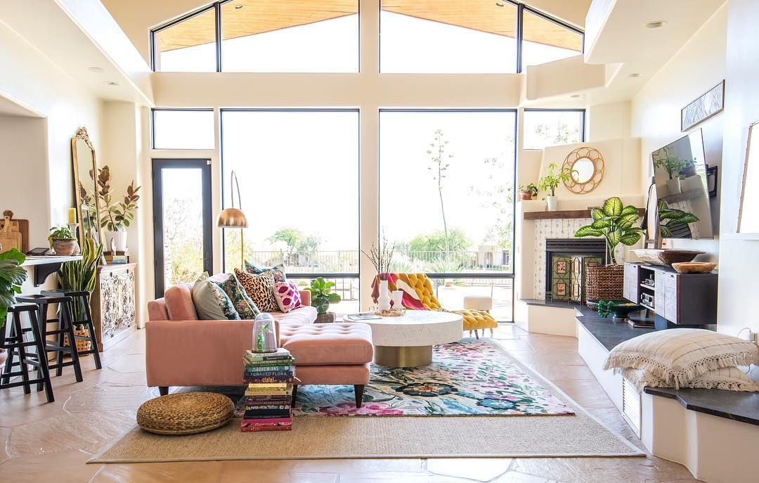 Large, special shape windows and a hinged patio door come together for a wall of glass in eclectic living room