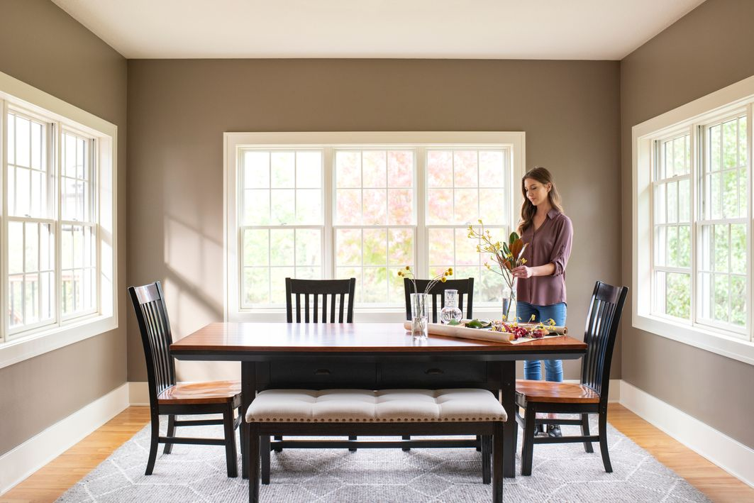 Woman arranging flowers in dining room area with white wood windows