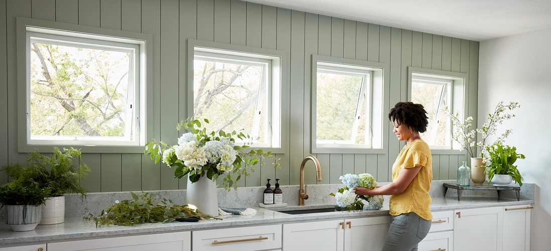 woman in a yellow shirt standing in kitchen by four awning windows