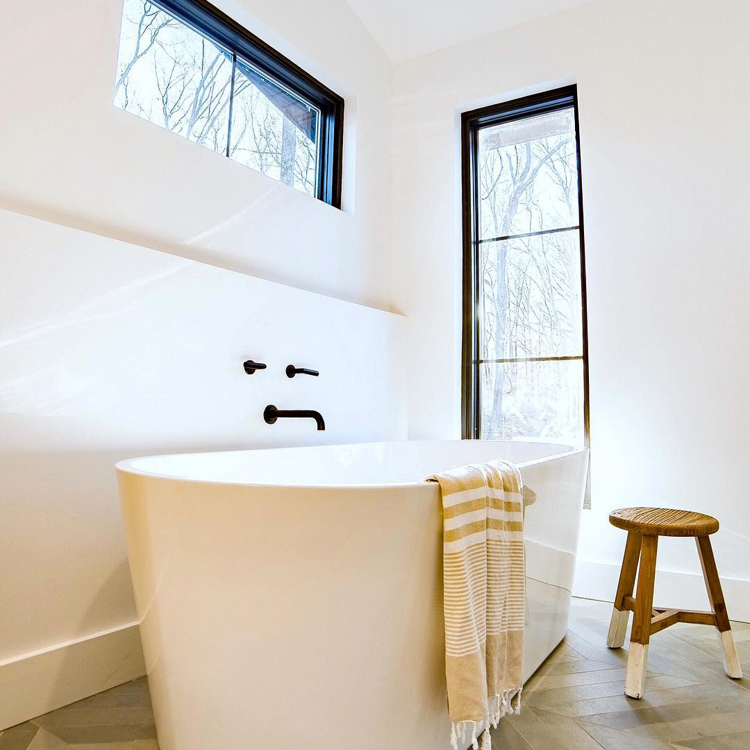 white bathroom with black windows framing a free standing tub