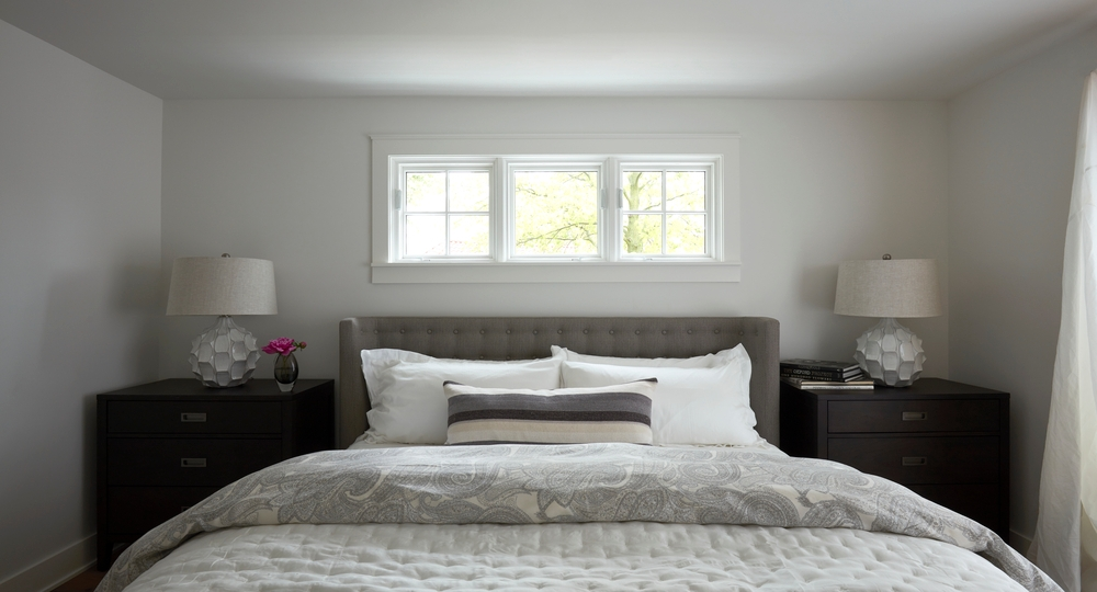 Perfectly made bed with three small square windows directly above and nightstands on either side