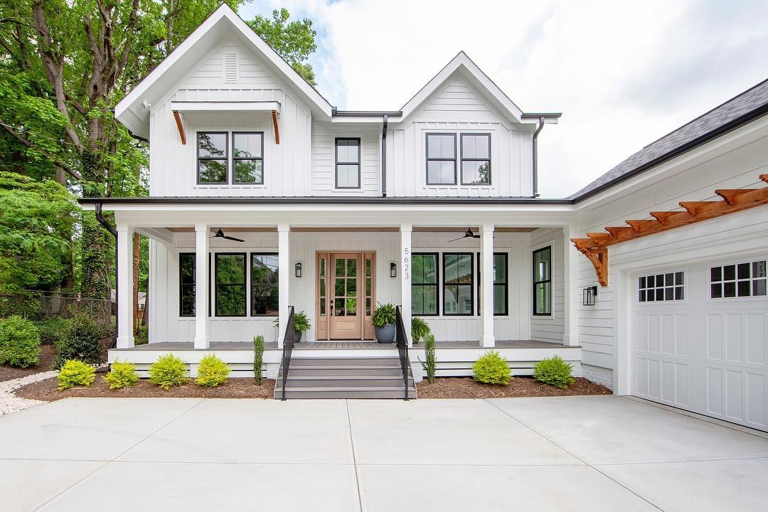 Two story modern farmhouse with white siding, black windows, and a wood front door