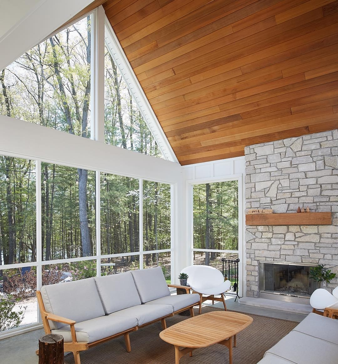 mid-century living room looks out to wooded backyard through wall of windows with triangle windows near ceiling