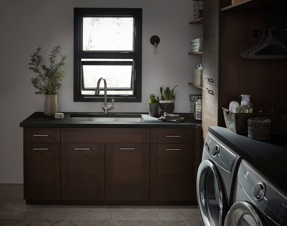 Laundry room with dark wood cabinets, black stacked awning windows, and gray washer and dryer