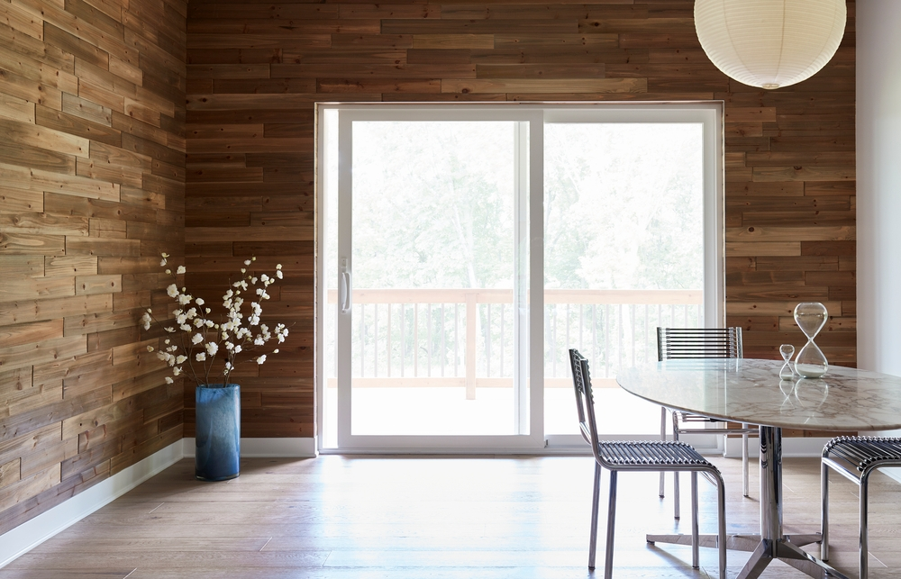 Dining room with wood plank walls, table and chairs, and white vinyl sliding patio door