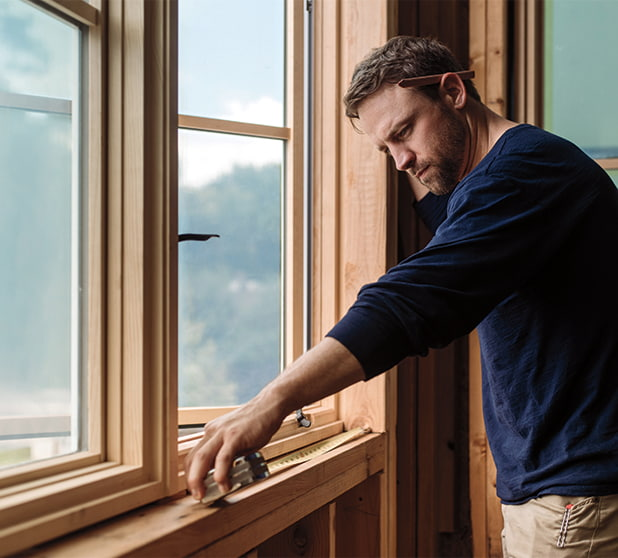 man in blue shirt measuring a wood window