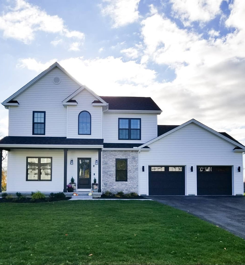A white farmhouse exterior features black double-hung and picture windows, including a custom arch window over the front door.