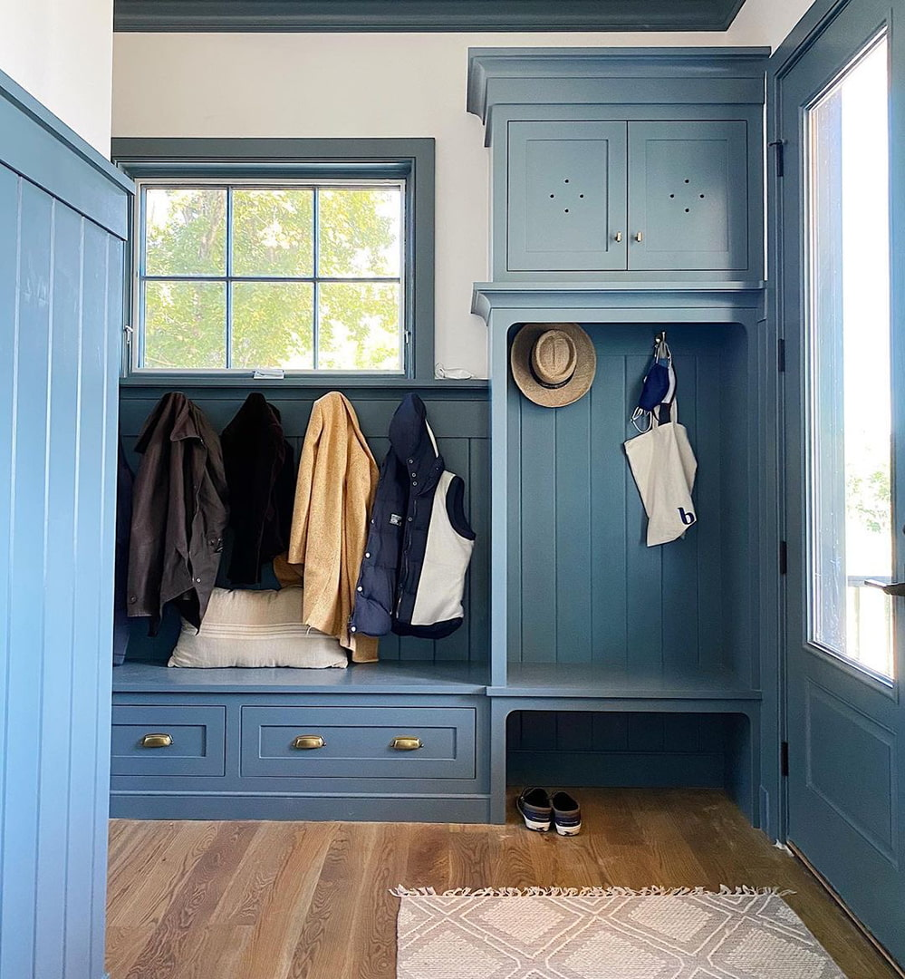 A mudroom with blue cabinets has an awning window above the coat hooks.
