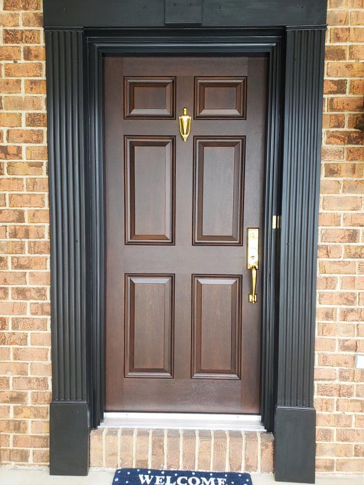 Brown front door with brass hardware and black trim on brick house