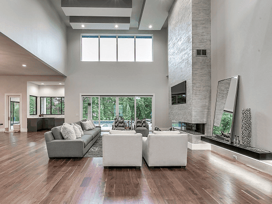 High ceiling gray living room with stone fireplace, white chairs, and stacked fixed windows over a sliding patio door