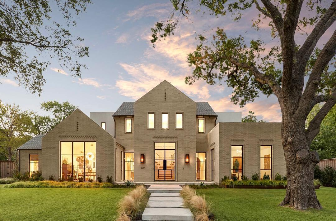 tan modern home at dusk with large windows and doors lit up