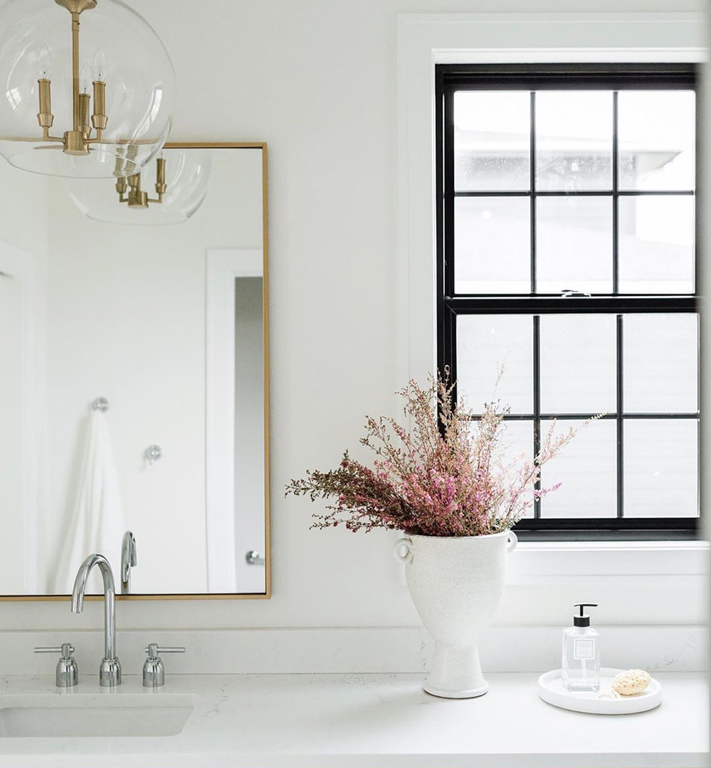 A black window in a light-colored bathroom invites natural light and brightness to the space.