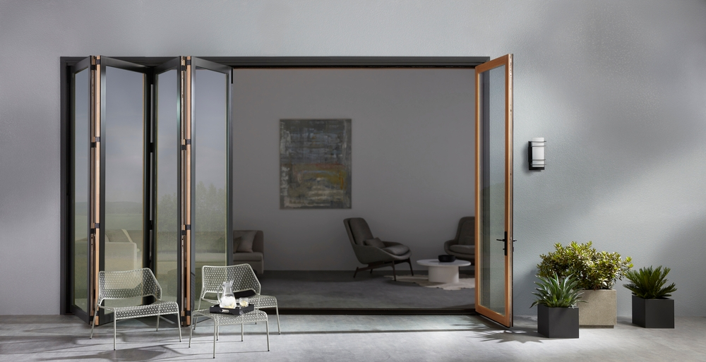 Black bifold patio door open and folded like an accordian on gray stucco home