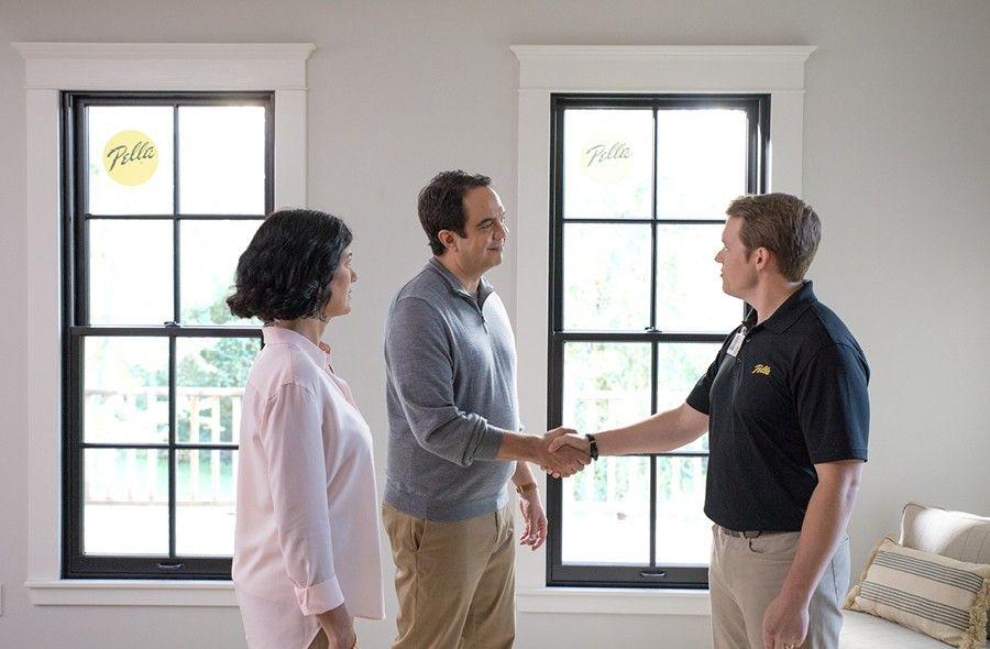 Pella consultant is shaking hands with a man in a gray shirt who stands next to his wife