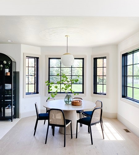 Black casement windows contrast against light interiors in modern breakfast nook.