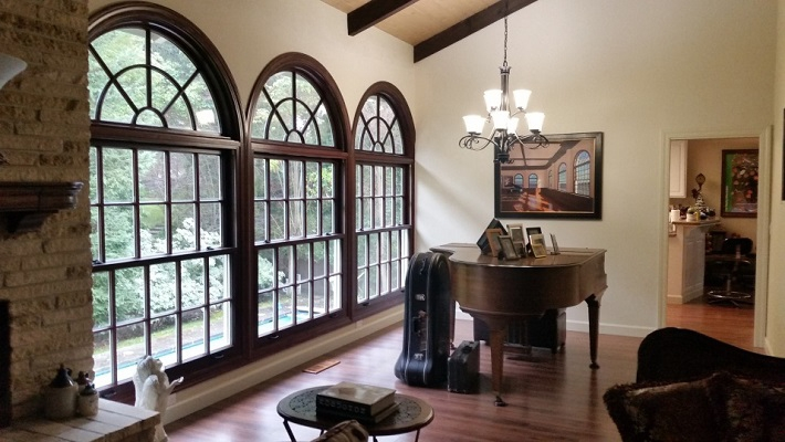 Wall of mahogany windows with half circle transoms above in piano room