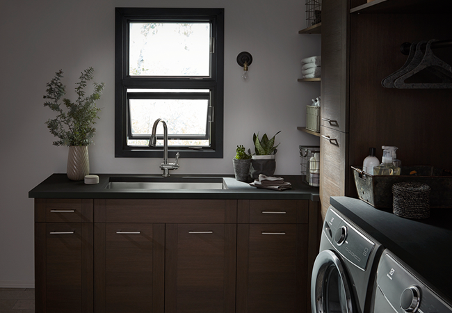 A laundry room with two stacked black awning windows above the sink.