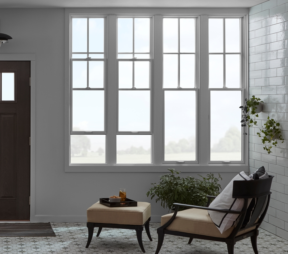 Four tall single-hung windows with chaise lounge chair underneath
